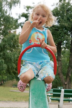 Pretty childhood girl swaying on the balance swing Stock Photo - 2326664