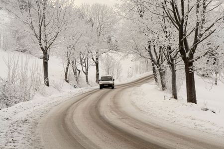 Slippery winter road with a turning among tree and mountains photo