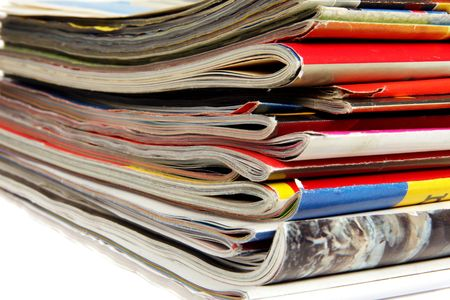 Stack of colorful magazines on light background