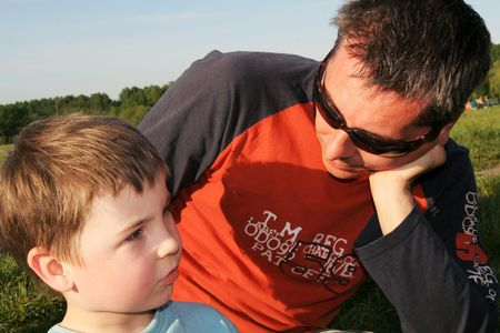 confiding: Father and son  having a conversation in an outdoor setting