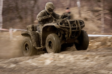 Man driving quad during the race among mud. photo