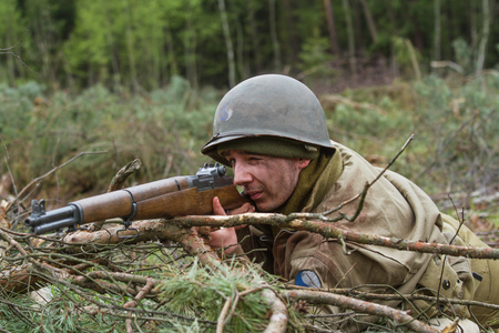 reenact: American World War II infantry soldier prepering for shooting