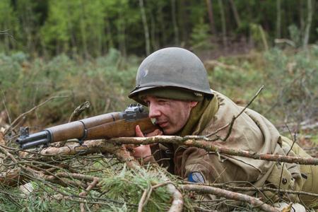world war ii: American World War II infantry soldier prepering for shooting