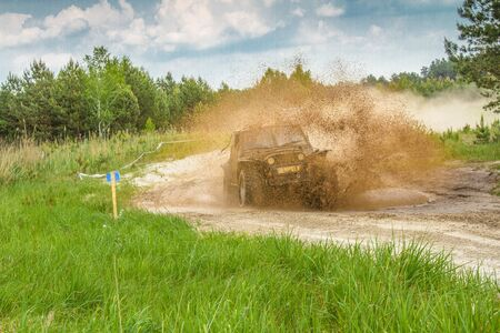 Off road. The vehicle splashing out the mud during off-road competition. Auto racing in spring