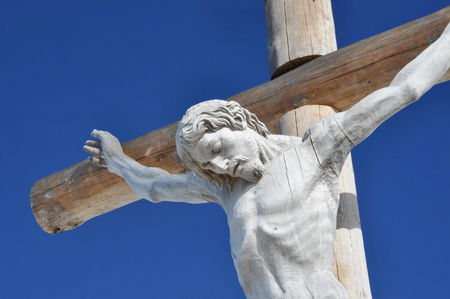 Cross with crucified Christ made out of wood located in Dolomites - Val Gardena, Seceda  photo