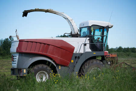 mowing grass with heavy agricultural machinery.
