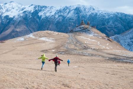 runing: Young girls runing over the hill in Tsminda Sameba Monastery, Kazbegi, Georgia