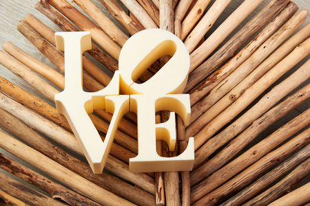 Plastic letters forming word LOVE written on wooden background.
