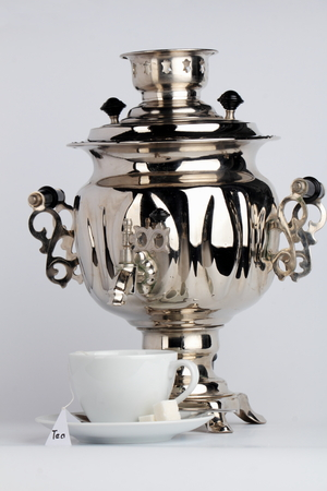 chromeplated: White tea cup with tea bag and chrome-plated samovar on a white background.