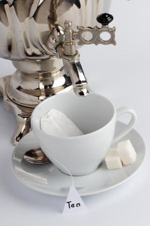 samovar: The spout of the samovar over a cup of tea with tea bag.