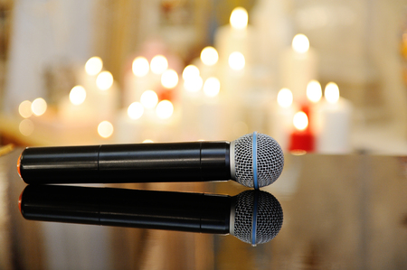 The microphone is on the polished piano lid. Against the backdrop of a beautiful blur of festive candles.
