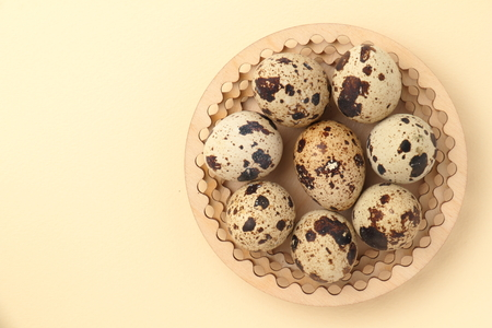 Quail eggs on a wooden plate. Beige background.