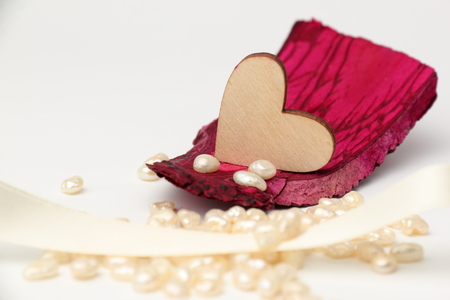 caoba: corazón de madera de caoba de madera a la deriva con las perlas en el fondo blanco. Foto de archivo