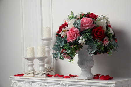 mantelpiece: Candles and a vase of flowers on the mantelpiece. Rose petals scattered over the fireplace.