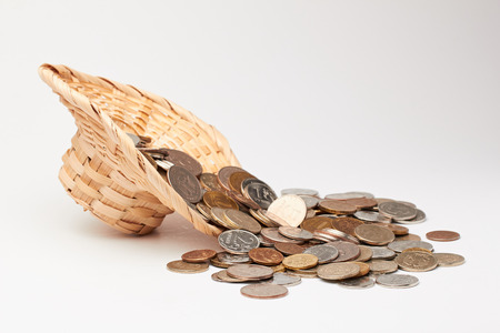 Wicker hat with coins on white background. Stock Photo