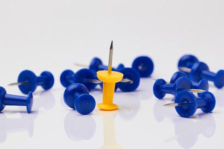yellow thumbtacks: Blue and yellow thumbtacks on a white background. Stock Photo