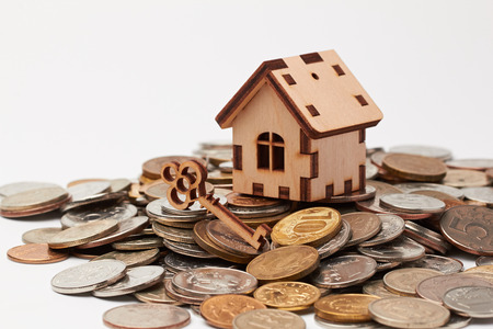 escrow: Wooden house and key on the coins.