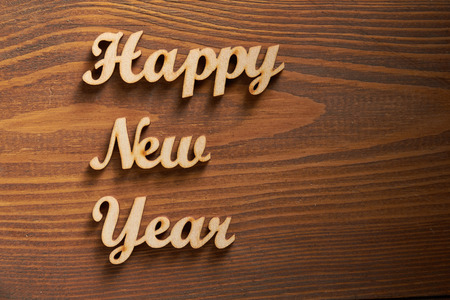 letterpress blocks: Happy New Year! - A phrase with wooden letters on a wooden background. Stock Photo
