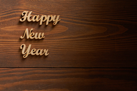 Happy New Year! - A phrase with wooden letters on a wooden background. Stock Photo
