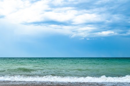 cloudy blue sky leaving for horizon above a blue surface of the sea Stock Photo