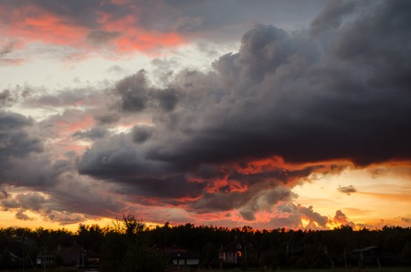 sunset clouds: beautiful sunset with dark gray clouds. red glare Stock Photo