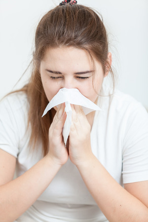 Ortrait of brunette woman sneezing in paper tissue Stock Photo - 26749263