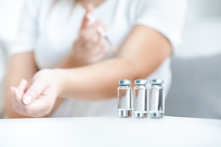 Shot of glass bottles with insulin against woman doing prick photo
