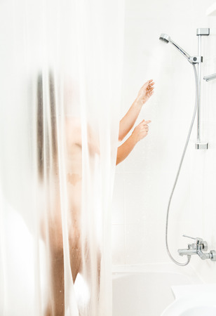 Brunette woman washing in shower behind transparent curtain photo
