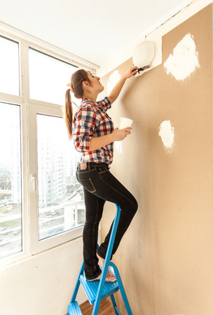 Woman plastering wall on high ladder photo