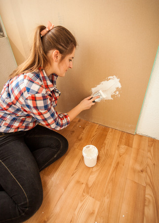 putty knives: Brunette woman doing house renovation