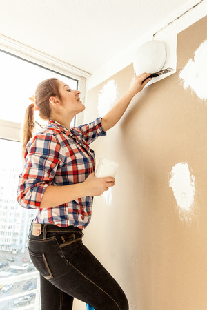 Female painter plastering gypsum cardboard wall photo