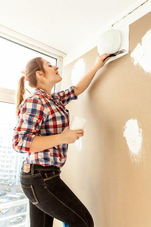 caulk: Female painter plastering gypsum cardboard wall Stock Photo