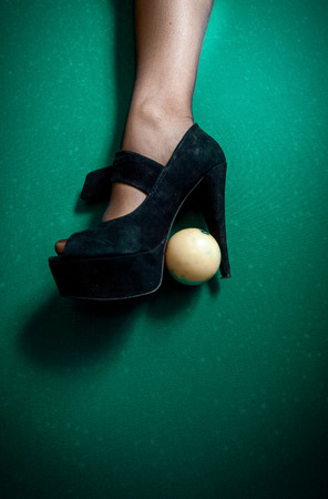 White billiard ball stuck in high heel black shoe photo