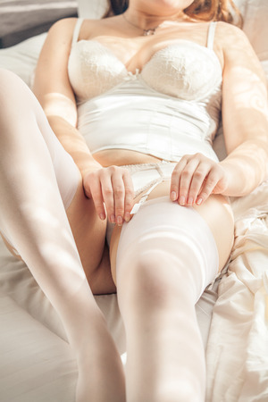 Closeup portrait of sexy woman wearing white stockings in bed photo