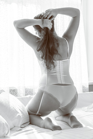 Black and white rear view of sexy woman in lingerie kneeling at bed against window Stock Photo