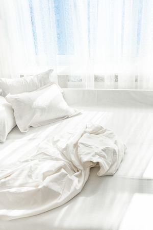 Photo of unmade bed against window photo