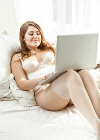 Beautiful woman in lingerie using laptop in bed photo