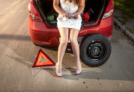 screw jack: Closeup photo of woman browsing on tablet how to fix broken car Stock Photo