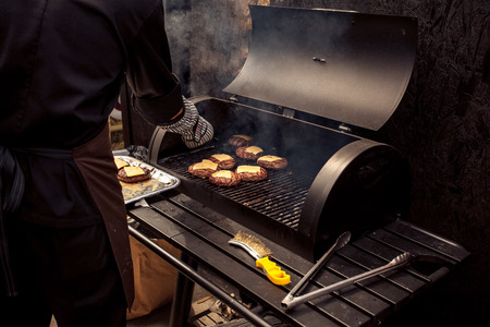 Outdoor shot of man cooking meat for cheeseburger on grill photo