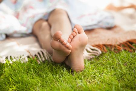Kleine meisjes voeten liggend op gras op zonnige dag