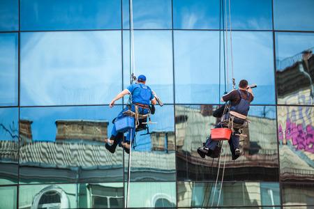 Two men cleaning window facade of skyscraper