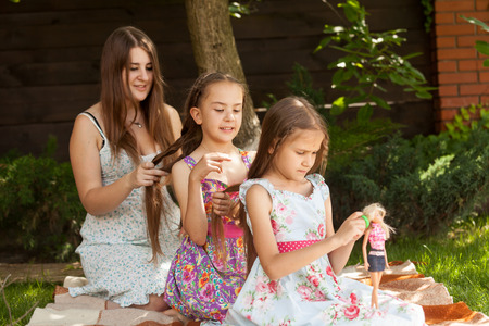 Three sisters sitting in front of each other and braiding hair at yard Stock Photo