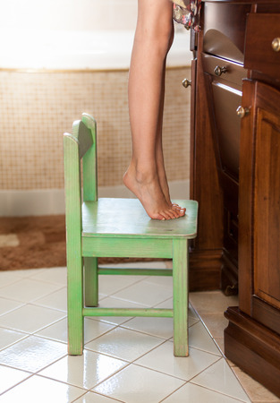 Closeup photo of little girl standing on tiptoes on chair at bathroom photo