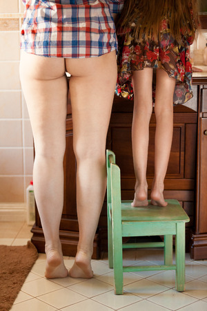 Closeup photo of feet of mother and daughter brushing teeth at morning