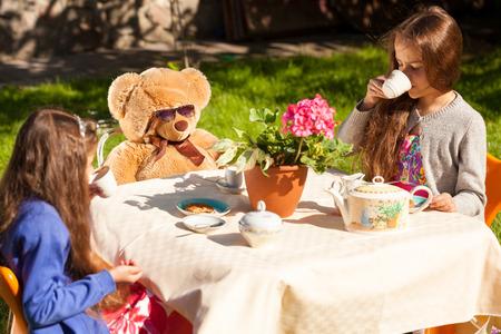 comida inglesa: Dos pequeñas hermanas que tienen el desayuno Inglés con un oso de peluche en el patio