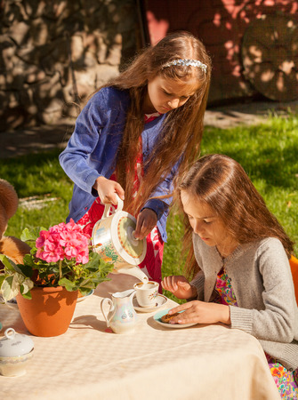 Two little girls playing in teatime at yard photo