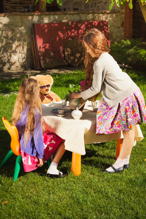 Two cute girls having tea party at yard photo