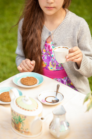 Beautiful brunette girl drinking tea at cafe terrace photo