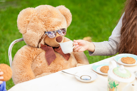 lawn party: Cute girl giving tea to teddy bear at yard Stock Photo