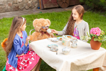 lawn party: Two girls having tea party with teddy bear at yard